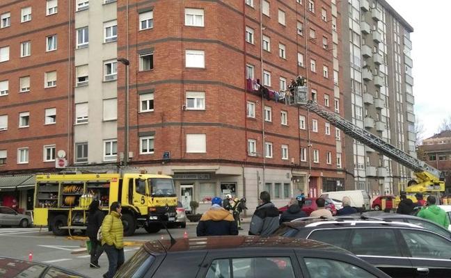 Los bomberos rescatan a una mujer del incendio de su vivienda en Versalles, Avilés