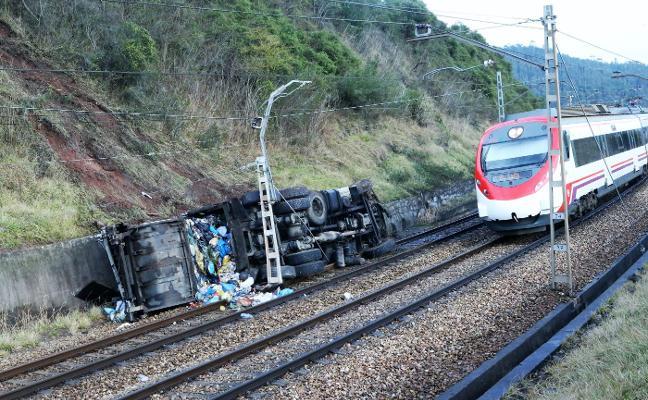 Salvan su vida al saltar del camión de basura que cayó a la vía del tren por un terraplén en Llanera