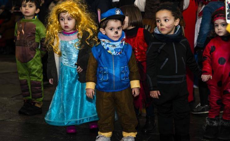 Los niños de Cangas de Onís se refugian de la lluvia bajo sus disfraces
