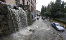 Una fuerte tromba de agua vuelve a desbordar el reguero del barrio de Cataluña, en Trubia
