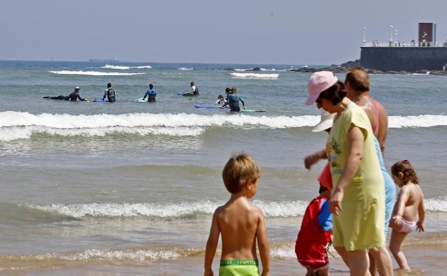 Surfistas y bañistas se dividen la playa en Gijón