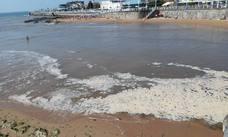 El río Piles de Gijón, marrón y con espuma tras las tormentas