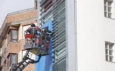 El viento obliga a los bomberos a asegurar unas chapas en Gijón