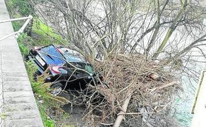 Ilesos tras caer con su coche al Nalón en Sama