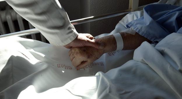 Un médico coge la mano de un paciente en una unidad hospitalaria de cuidados paliativos. / JOSÉ SIMAL
