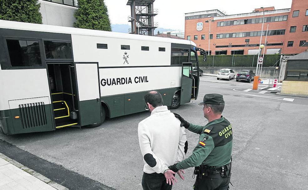 Un sargento de la Guardia Civil introduce a un hombre en el autobús de traslados / FOTOS JORGE PETEIRO