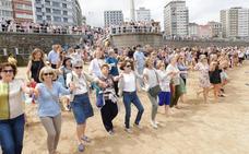 Gijoneses y turistas, unidos al ritmo de la Danza Prima