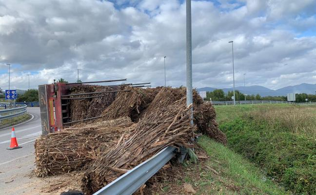 Un camión con biomasa vuelca en la rotonda de entrada a Navia