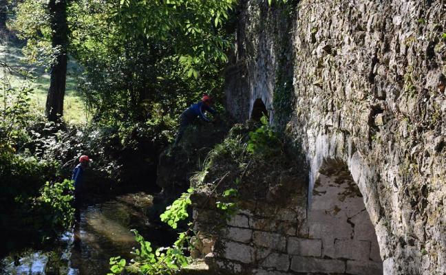 Una empresa realiza tareas de limpieza y desbroce del puente medieval de El Romanón