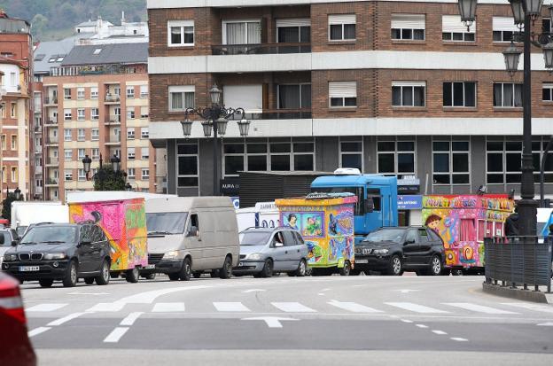 Caravana de feriantes, muchos de ellos con sus atracciones a remolque, ayer en el centro de Oviedo. / ÁLEX PIÑA