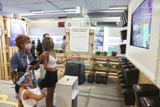 Varias personas participan en el juego de selección de reciclaje de  Cogersa para adquirir de regalo  un cubo marrón para residuos orgánicos, en conmemoración del  Día del Medio Ambiente./ DAMIÁN ARIENZA