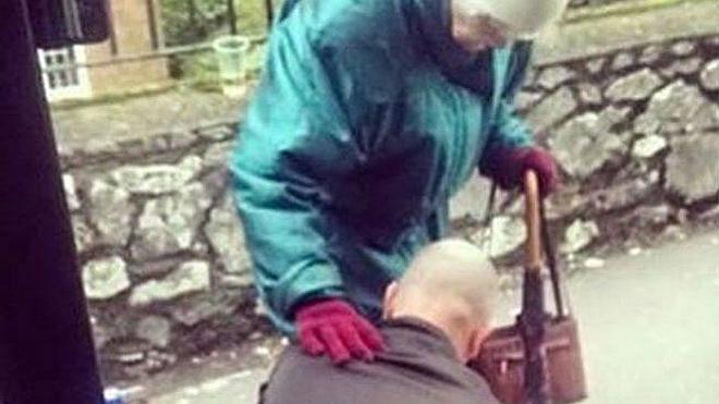 Un conductor se baja del autobús para ayudar a una anciana a atarse los cordones